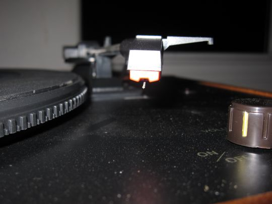 Close up photo shows the stylus (needle) and cartridge of the Crosley CR249 turntable.