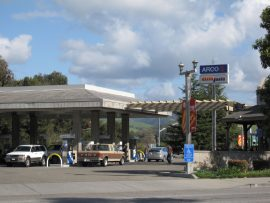 A wide angle photo of an ARCO station. ARCO and am/pm sign towers above the busy gas station.